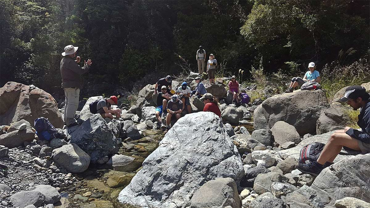 Group of students on riverbed listening to tutor